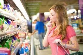 Người tiêu dùng mua hàng trên giá kệ siêu thị